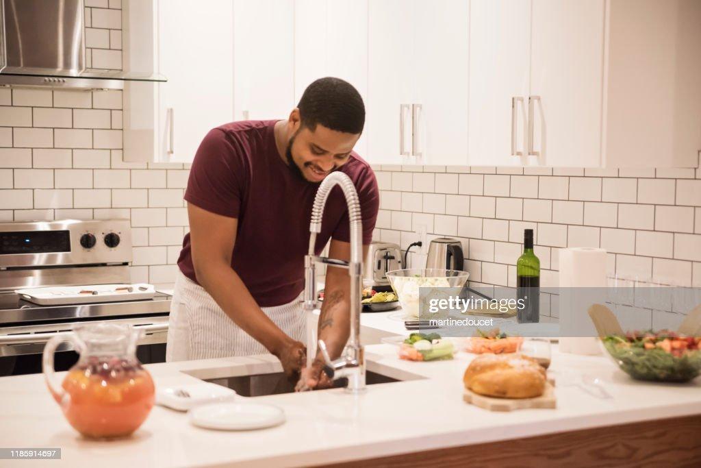 African-American man washing hands before preparing Thanksgiving dinner. : Stock Photo