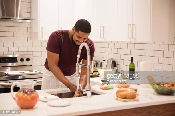 """afroamerikanischer mann, der händeseitfest ist, bevor er thanksgiving dinner zubereitet. - """"martine doucet"""" or martinedoucet stock-fotos und bilder"""
