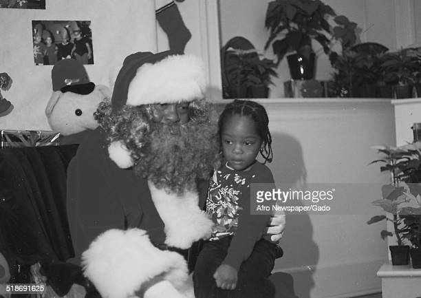 AfricanAmerican man wearing a Santa Clause suit during a Christmas party 1995