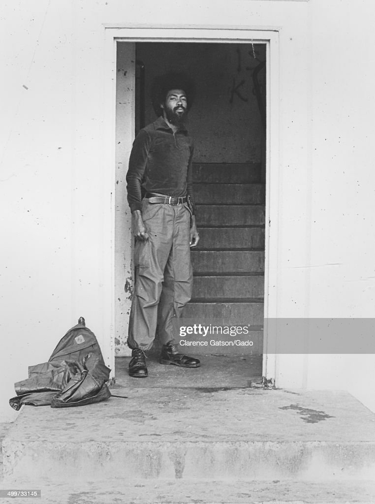 African-American man wearing army boots and Afro haircut, posing in a doorway, San Francisco, California, 1980.