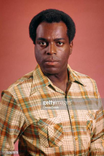 AfricanAmerican Man Wearing Plaid Shirt Looking At Camera With Direct And Sincere Facial Expression