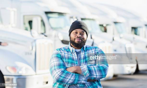 african-american man with fleet of semi-trucks - macho stock pictures, royalty-free photos & images