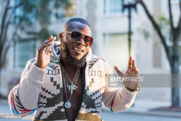 african-american man with gold grill on city street - rap stock pictures, royalty-free photos & images