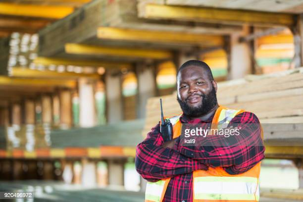african-american man working in a lumberyard - fat black man stock photos and pictures