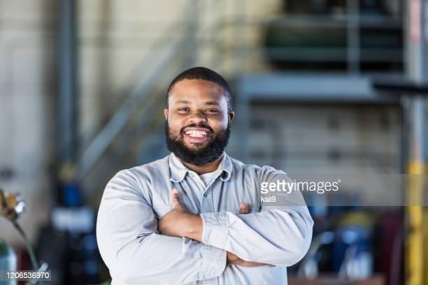 homem afro-americano trabalhando em oficina - gordo - fotografias e filmes do acervo