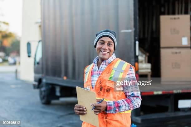 African-American man working, with delivery truck