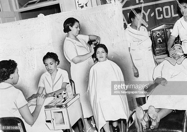 AfricanAmerican members of the Apex Barbar and Beauty School cutting the hair of a client in a barber shop 1944