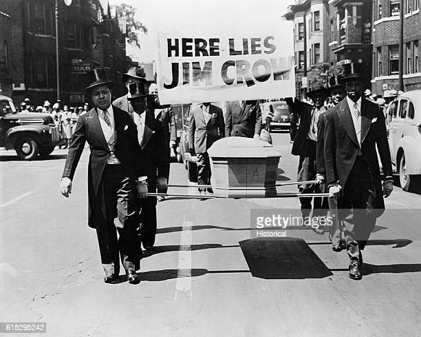 AfricanAmerican men wearing tuxedos carry a coffin and a Here Lies Jim Crow sign down the middle of a street as a demonstration against Jim Crow...