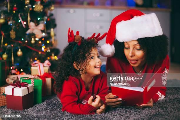 madre afroamericana y su hija pequeña leyendo un libro junto a un árbol de navidad en la sala de estar en invierno - historia fotografías e imágenes de stock