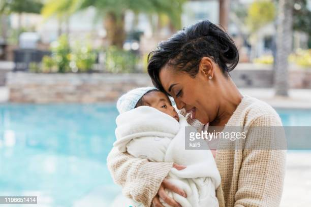 african-american mother with baby boy wrapped in blanket - avvolto in una coperta foto e immagini stock