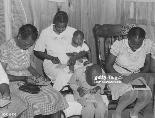 AfricanAmerican mothers with children gathered to play bingo Madison Parish Louisiana USA 1940 From the New York Public Library