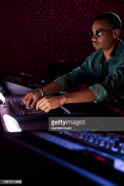 african-american music producer mixing song on sound mixer control panel in music studio - post-production stock pictures, royalty-free photos & images
