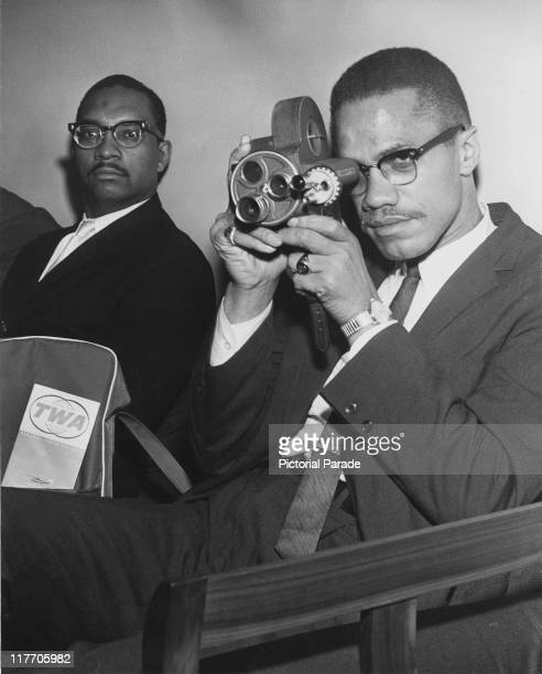 AfricanAmerican Muslim minister and civil rights activist Malcolm X holding a movie camera while waiting for a flight to London from John F Kennedy...
