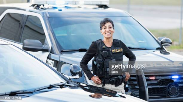 african-american policewoman standing by patrol car - police force stock pictures, royalty-free photos & images