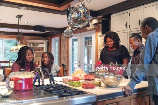 african-american preparing thanksgiving dinner - canadian thanksgiving stock pictures, royalty-free photos & images