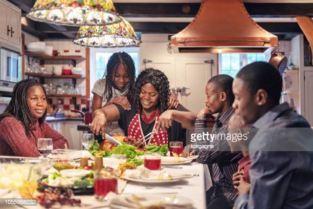 african-american preparing thanksgiving dinner - black family dinner stock photos and pictures