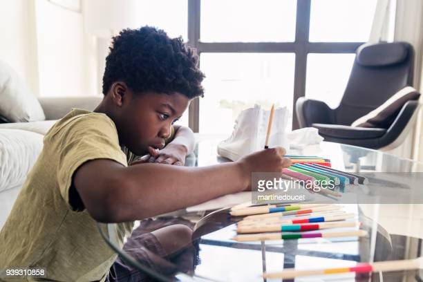 African-american preteen kid doing a craft project.