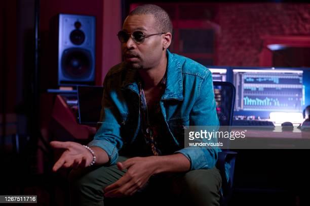 afroamerikanischer produzent spricht mit künstler über den musiktrack im musikstudio - produzent stock-fotos und bilder