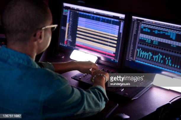 african-american producer working on music track on sound mixer control panel in music studio - industry stock pictures, royalty-free photos & images