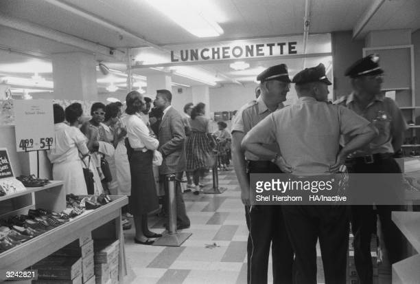 AfricanAmerican protesters congregate at Brown's Basement Luncheonette during a sitin while Caucasian police officers observe Oklahoma