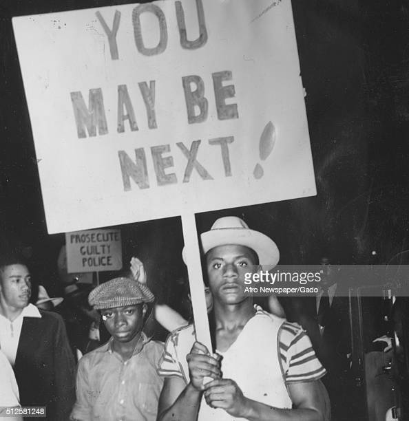 African-American protesters holding signs reading 'You May Be Next' and marching in a protest against police brutality after the shooting death of an...