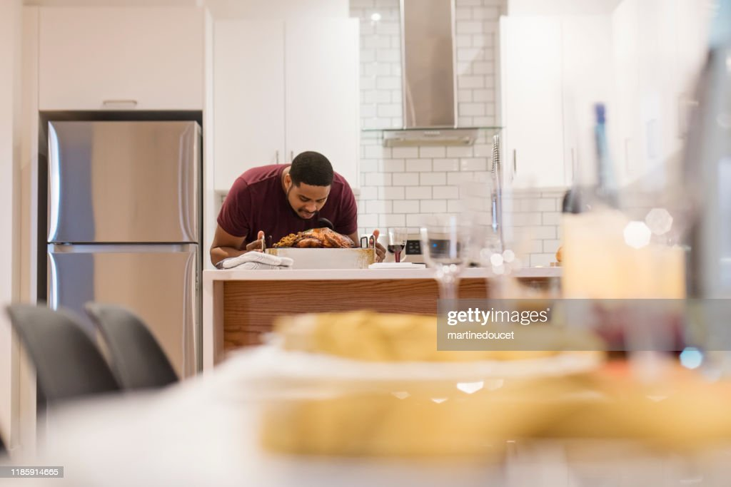 African-American smelling turkey for Thanksgiving dinner. : Stock Photo
