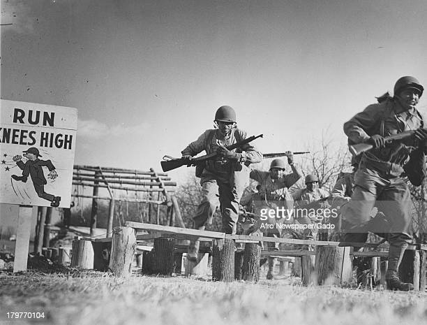 AfricanAmerican soldiers in full gear and toting guns run obstacle course they constructed at Aberdeen Proving Grounds army base Aberdeen Maryland...