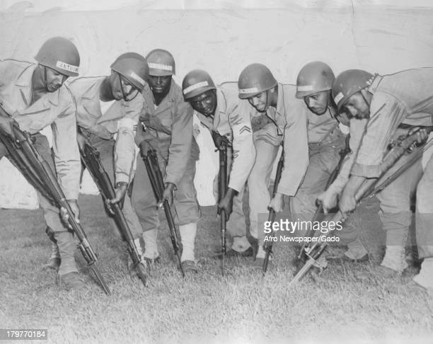 AfricanAmerican soldiers point rifles fixed with bayonets at the ground at Aberdeen Proving Grounds Aberdeen Maryland October 7 1944
