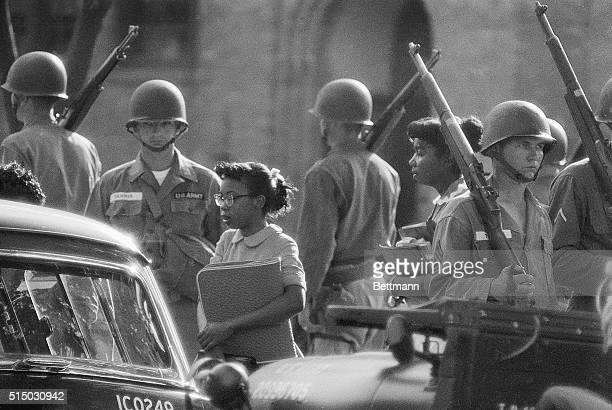 African-American students attending Little Rock Central High School are escorted to a waiting Army station wagon for their return home after classes,...