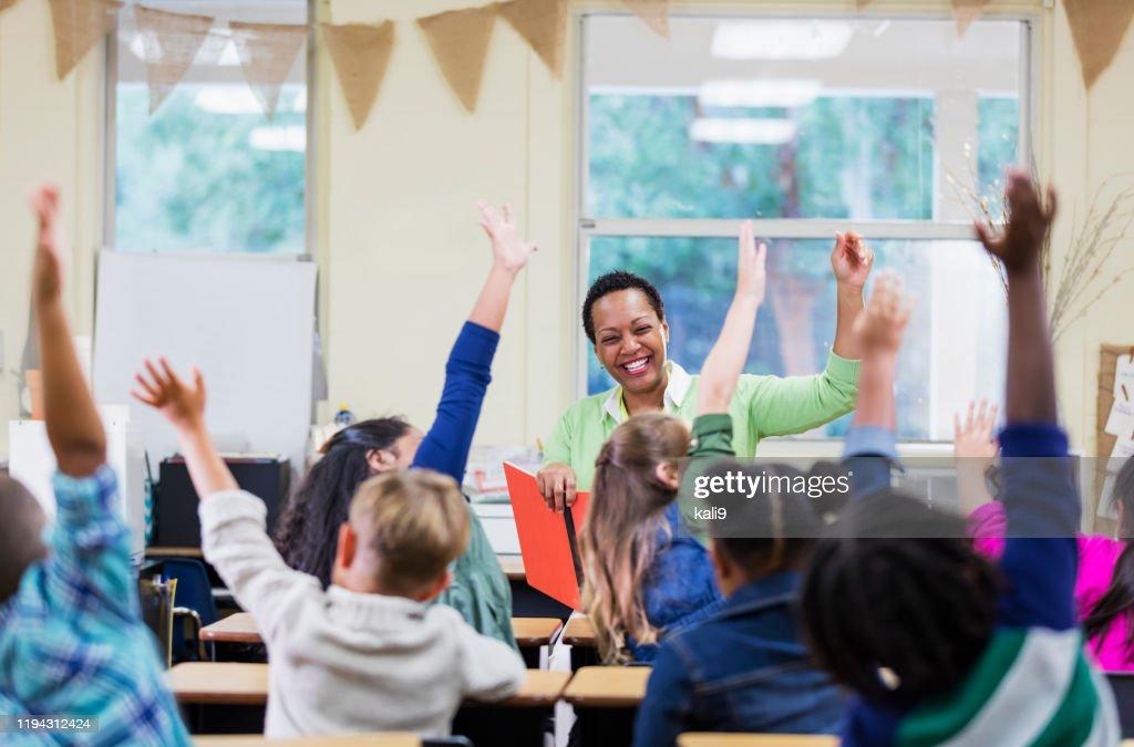 African-American teacher reading to school children : Stock Photo