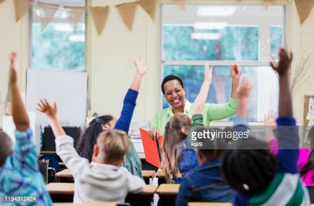 african-american teacher reading to school children - affectionate stock pictures, royalty-free photos & images