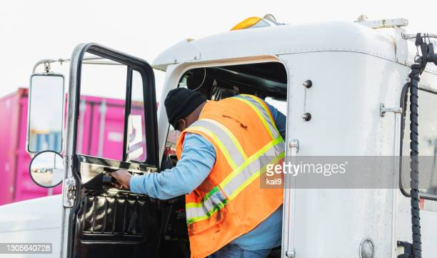 african-american truck driver climbing into semi-truck - entering stock pictures, royalty-free photos & images