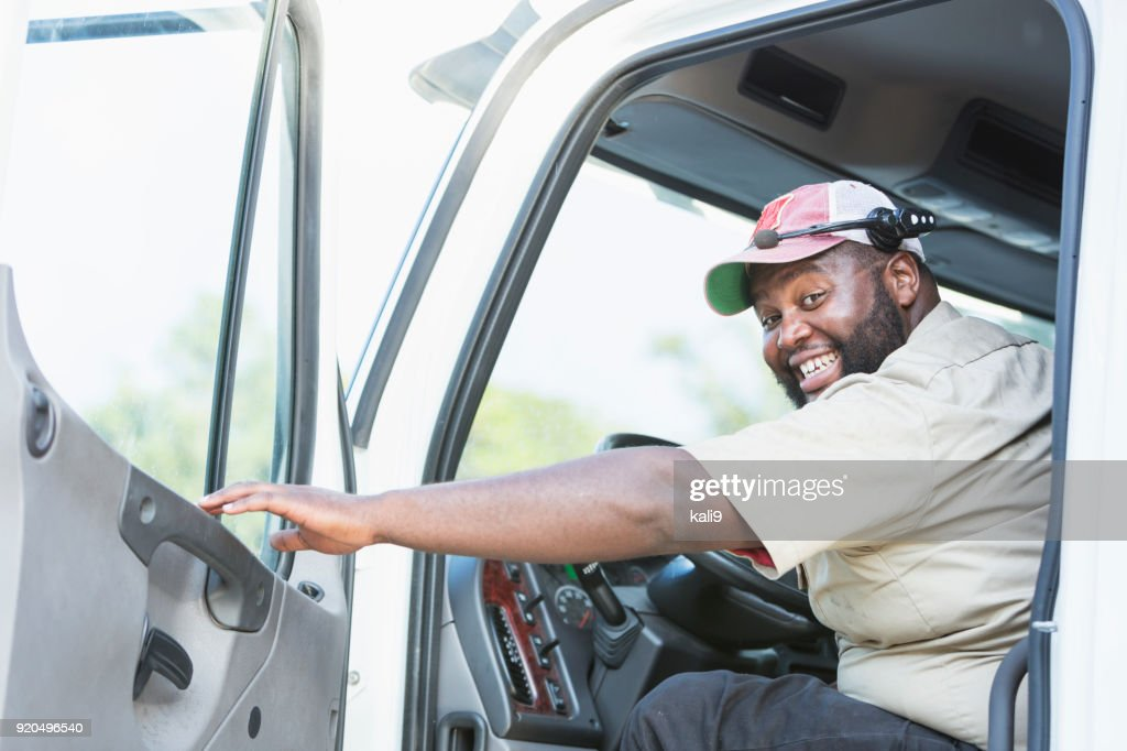 African-American truck driver in driver's seat : Stock Photo
