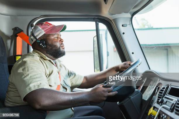 african-american truck driver in driver's seat - fat black man stock photos and pictures
