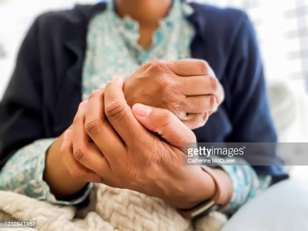 african-american woman bothered by dry skin rubs her hands - huidaandoening stockfoto's en -beelden