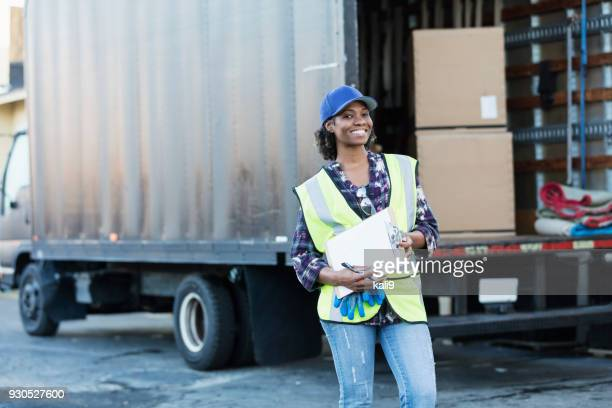 African-American woman by delivery truck, with clipboard