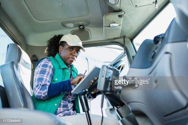 african-american woman driving a semi-truck - shirt stock pictures, royalty-free photos & images