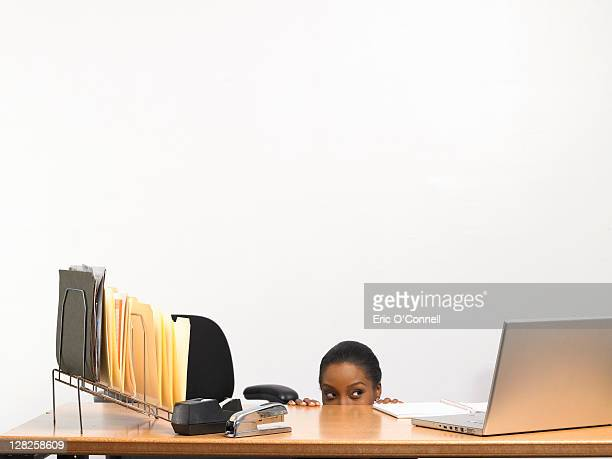 African-American woman hiding behind desk