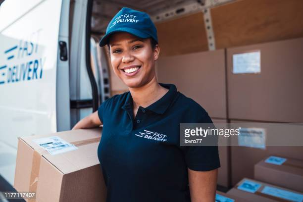 african-american woman holding a delivery package - postal worker stock pictures, royalty-free photos & images