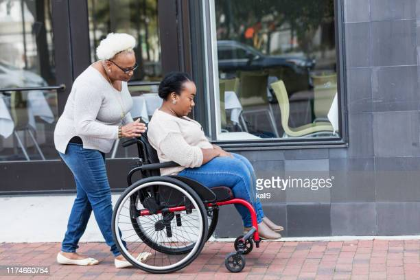 african-american woman in wheelchair with mother in city - emotional support stock pictures, royalty-free photos & images