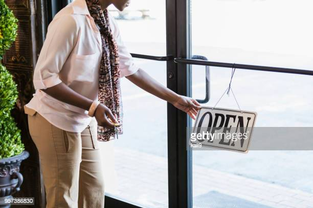 African-American woman opening store, turning sign