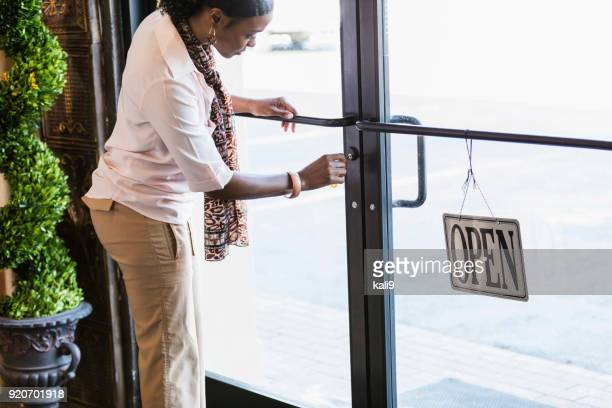 african-american woman opening store, unlocking the door - cartello chiuso foto e immagini stock