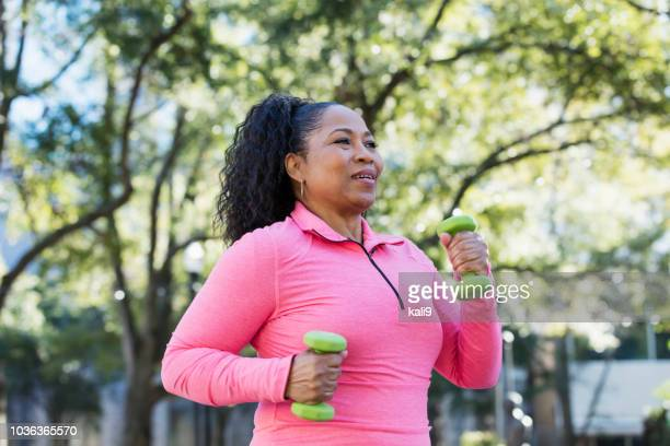 african-american woman powerwalking with hand weights - beautiful fat women stock pictures, royalty-free photos & images