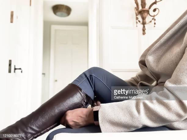 african-american woman pulls on leather riding boots - schwarze hosen stock-fotos und bilder