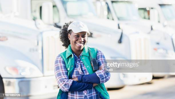 african-american woman standing in front of semi-trucks - truck driver stock pictures, royalty-free photos & images