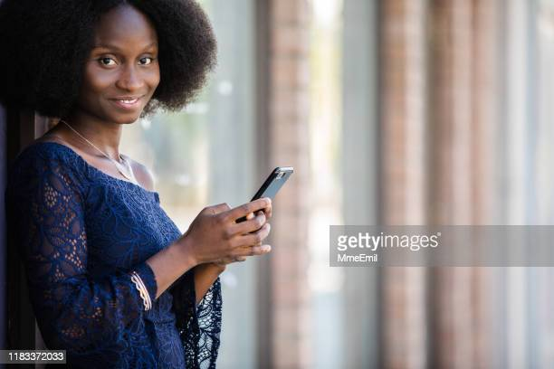african-american woman texting on the street - mmeemil stock photos and pictures