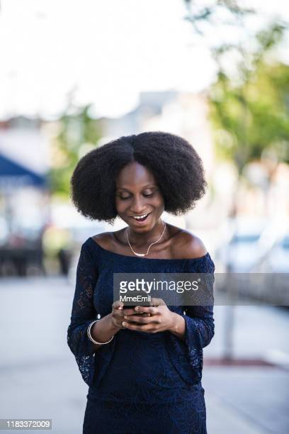 african-american woman using smartphone on-the-go - mmeemil stock photos and pictures