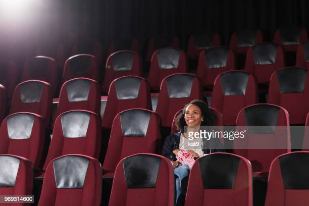 african-american woman watching movie in theater alone - seat stock pictures, royalty-free photos & images