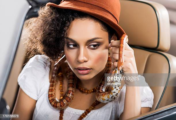 african-american woman with snake sitting in car. - black snake stock pictures, royalty-free photos & images