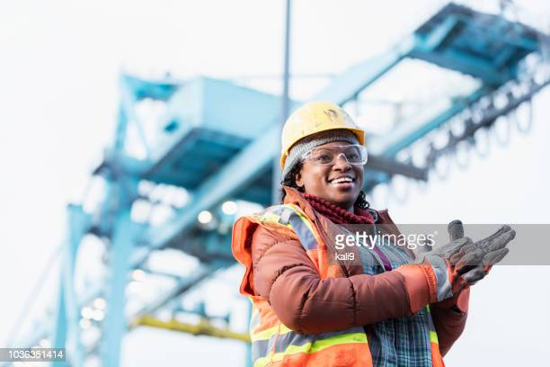 african-american woman working at shipping port - work glove stock photos and pictures
